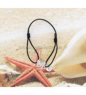 Pulsera elástica ajustable con una mariposa de acero decorada con diamantes de imitación y un amuleto de Eye of Saint Lucia.